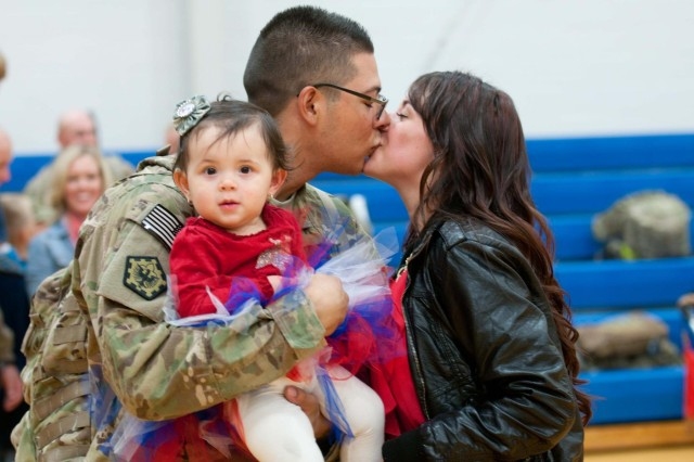 Amanda and her one year old daughter, Sophia, welcome home husband and father, Pfc. Alexander Avila, Headquarters and Headquarters Company, 555th Engineer Brigade, with a smooch on the lips at Wilson Sports and Fitness Center, Oct. 4. The 555th Engineer Bde., HHC, completed a nine-month deployment to Afghanistan in support of Operation Enduring Freedom.