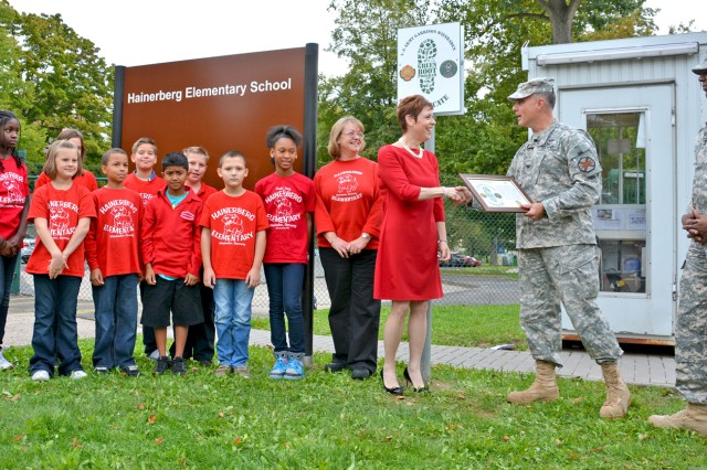 Col. David Carstens, U.S. Army Garrison Wiesbaden commander, presents Hainerberg Elementary School Principal Penelope Miller-Smith and members of the school's Recycling Club with the Green Boot certificate for their outstanding environmental program.