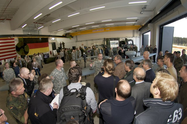 A member of the Hunter UAS operations crew takes questions from the German press regarding flight safety during the open house of the new Joint Multinational Training Command (JMTC) UAS facility Oct. 8th, 2013 on Rose Barracks in Vilseck, Germany. During the event, German dignitaries, political representatives and members of the press toured the new facility at the invitation of the JMTC and U.S. Army Garrison Bavaria commanders. BG Piatt (far left) encouraged the press to speak directly with the U.S. and German Bundeswehr Soldiers in attendance who were on hand to explain how JMTC trains UAS operators at its Grafenwoehr and Hohenfels Training areas. (U.S. Army Photo by Michael Beaton/Released).