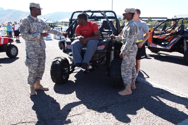 "Soldiers from Company A, 2-13th Aviation Regiment, explore an all-terrain vehicle at the ""Bikes and Bands"" Street Fair Saturday. The fair featured bike and all-terrain vehicle dealership displays, biker and sports gears vendors."