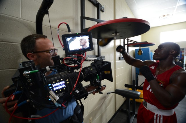 """U.S. Army World Class Athlete Program boxer Spc. Marquis Moore is filmed during a workout at the """"House of Pain"""" boxing facility on Fort Carson, Colo., for an MTV spot on National Hispanic Heritage Month, featuring WCAP assistant boxing coach Staff Sgt. Alexis Ramos."""