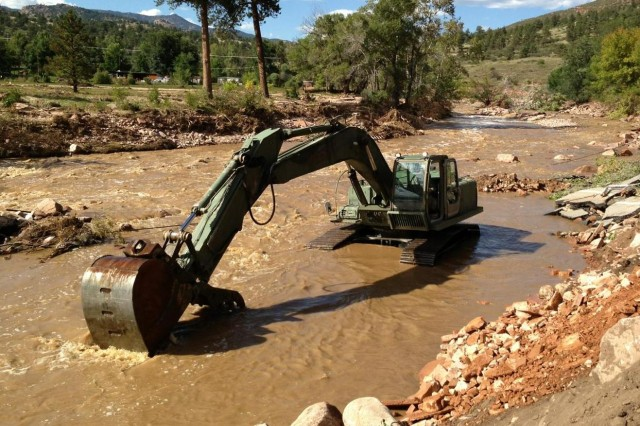 The Texas Army National Guard's 36th Infantry Division's Domestic All-Hazards Response Team-West continues to coordinate assistance requests and support for the Colorado flood relief effort. Pictured here, a military hydraulic excavator works to clear the remainder of a Colorado road after a flood washed it away. Many roads were destroyed during the Colorado flood leaving some Colorado residences stranded and forced to backpack in fuel and food to their homes.