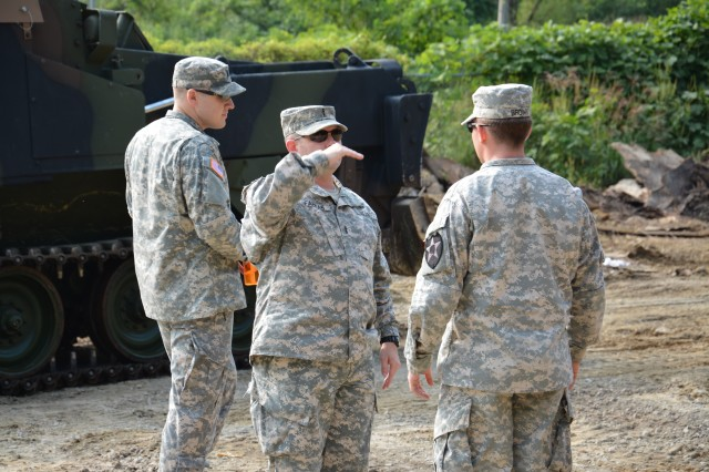 Chief Warrant Officer 4 Jeffery D. Farkas (middle), of Middletown, Ohio, 210th Fires Brigade targeting officer, explains to Sgt. Anthony Brown (right), of  Rochester, Ind., a field artillery firefinder radar operator assigned to 333rd Field Artillery Target Acquisition Battery, 1st Battalion 38th Field Artillery Regiment, 210th Fires Bde., 2nd Inf. Div., how high he will like the berm to be for the enhanced survivability position at Seong ji Gol Village on Sept. 16 at Camp Casey.