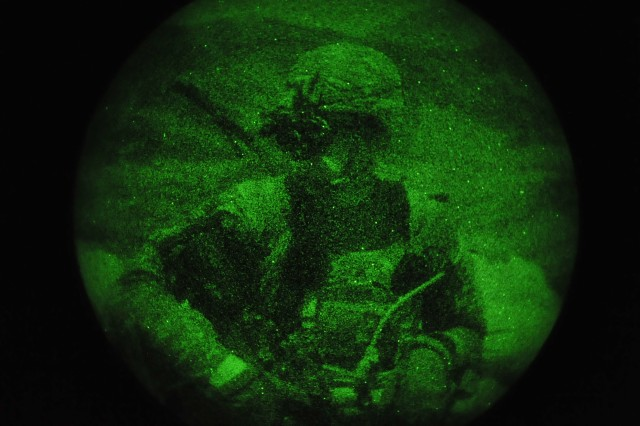 Sgt. Michael Peterson, an infantryman and an native of Winder, Ga., with 2nd squad, 3rd Platoon, Company C, 2nd Battalion, 30th Infantry Regiment, 4th Brigade Combat Team, 10th Mountain Division, uses his night vision devices to survey as he mans the teams radio while standing guard on a night observation post on Forward Operating Base Torkham, in Nangahar Province, Afghanistan, Sept. 27, 2013.