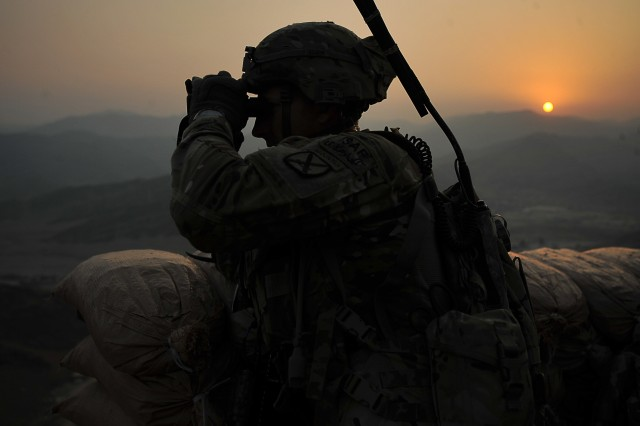 Staff Sgt. Shelby Johnson, squad leader with 2nd squad, 3rd Platoon, Company C, 2nd Battalion, 30th Infantry Regiment, 4th Brigade Combat Team, 10th Mountain Division, uses a set of binoculars to survey the surrounding area as the sun comes up after standing guard on a night observation post on Forward Operating Base Torkham, in Nangahar Province, Afghanistan, Sept. 27, 2013.