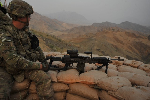 Pfc. Justin Singleton, an infantryman with 2nd squad, 3rd Platoon, Company C, 2nd Battalion, 30th Infantry Regiment, 4th Brigade Combat Team, 10th Mountain Division, and a native of Deland, Fla., surveys the surrounding area before heading down the mountain after spending the night on a night observation post on Forward Operating Base Torkham, in Nangahar Province, Afghanistan, Sept. 27, 2013.
