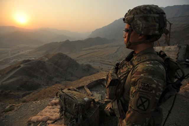 Spc. Dali Carrillo, a native of Winston Salem, N.C., who serves as an infantryman with 2nd squad, 3rd Platoon, Company C, 2nd Battalion, 30th Infantry Regiment, 4th Brigade Combat Team, 10th Mountain Division, watches the sun rise before heading down the mountain after spending the night on a night observation post on Forward Operating Base Torkham, in Nangahar Province, Afghanistan, Sept. 27, 2013.