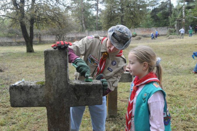 Boy Scout Joshua Saxton and Girl Scout Brigitte Schnell sport Polish neckerchiefs on their uniforms to honor the POWs once buried here while scrubbing down a headstone during the Kontakt Club's annual cleanup of the Polish cemetery at Hohenfels, Oct. 5.