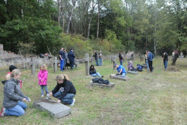 "Volunteers from throughout the Hohenfels Military Community joined the Hohenfels German American Kontakt Club in their annual ""Make a Difference Day"" project of cleaning the Polish prisoner of war cemetery on post, Oct. 5."