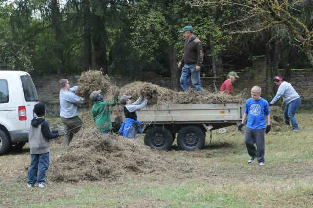 Volunteers load trailers full of grass and debris during the Kontakt Club's annual cleanup of the Polish cemetery at Hohenfels, Oct. 5.