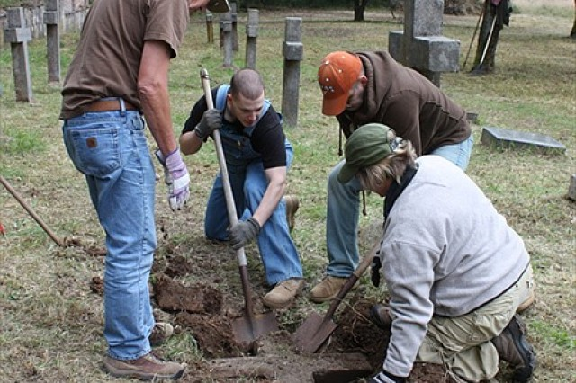 Volunteers uncover a previously buried headstone during the Kontakt Club's annual cleanup of the Polish cemetery at Hohenfels, Oct. 5.
