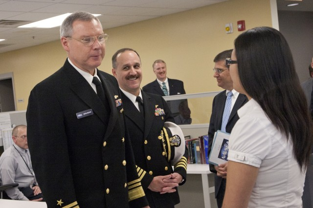 Vice Adm. Kevin McCoy (left), Capt. Andy Buduo (right), and former Technical Director, Mr. Dennis McLaughlin (far right), speak with Elizabeth Lee at Picatinny Arsenal.