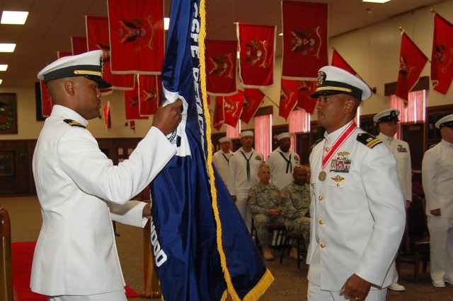 Navy Lt. Alberto Alshabazz, left, takes the colors of the Center for Seabees and Facilities Engineering Navy Detachment from outgoing commander, Navy Lt. Jeffery Turner, during a ceremony Friday.