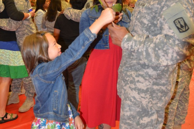 A Soldier from 4th Battalion, 3rd Air Defense Artillery receives a rose from a Family Member during the 4-3 ADA redeployment ceremony, Fort Sill, Okla.