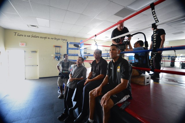 """U.S. Army World Class Athlete Program assistant boxing coach Staff Sgt. Alexis Ramos (seated far right) watches a video of himself boxing with his father, Rafael Ramos, a retired Army first sergeant and member of the Puerto Rico Boxing Hall of Fame, during an MTV shoot at the WCAP's """"House of Pain"""" boxing facility on Fort Carson, Colo."""
