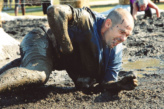 Matt Johnson slogs his way through the mud-crawl portion of the Krazy Krieger 5K Challenge Run as part of Fort Belvoir's 2013 Oktoberfest celebration Saturday.