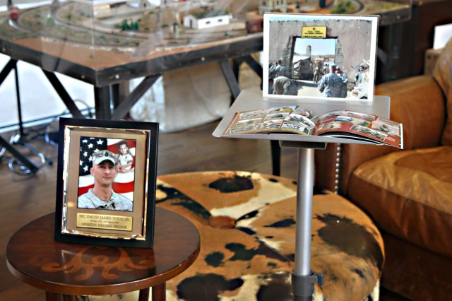 FORT SAM HOUSTON, Texas - Photos of Sgt. 1st Class David Todd Jr. adorn the tables Sept. 30 at the Warrior and Family Support Center as David and Mary Todd are presented a sign that honored the memory of their son. The sign previously hung outside of Forward Operating Base Todd in Afghanistan. Todd was killed Aug. 20, 2008 in Afghanistan. (U.S. Army photo by Sgt. Maj. Matthew Howard, Army North PAO)