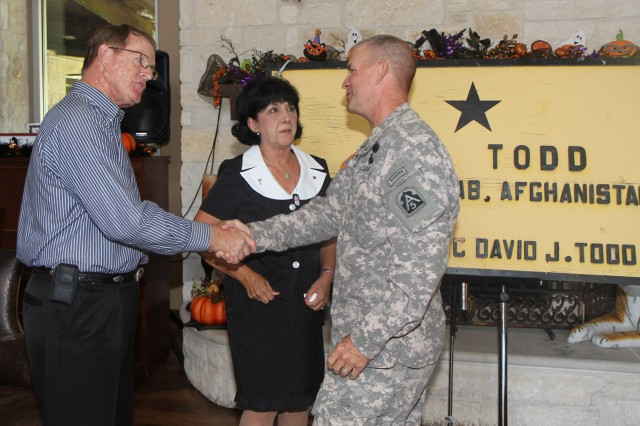 FORT SAM HOUSTON, Texas - Command Sgt. Maj. Hu Rhodes, senior enlisted leader for U.S. Army North (Fifth Army), Fort Sam Houston and Camp Bullis, expresses his condolences to David and Mary Todd following a ceremony Sept. 30 at the Warrior and Family Support Center. David and Mary were presented with a sign that previously hung outside of Forward Operating Base Todd in Afghanistan. The FOB was named after their son, Sgt. 1st Class David Todd Jr., who was killed Aug. 20, 2008 in Afghanistan. After the FOB closed, Mary Todd began a quest to track down the sign and bring it home. (U.S. Army photo by Staff Sgt. Corey Baltos, Army North PAO)