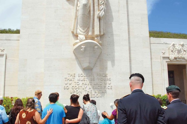 Family members of the fallen, along with USAG-HI leaders, pause at the base of the Lady Columbia, the site of the lei presentation at the lei of honor and remembrance ceremony at the National Memorial Cemetery of the Pacific, Sunday.