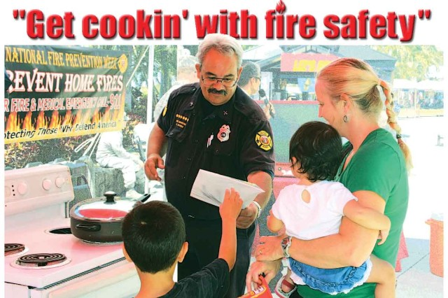 "SCHOFIELD BARRACKS "" A fire safety campaign firefighter tells a family how cooking is the leading cause of home fires, and to never leave the stove or oven unattended, during last year's Fire Prevention Week, here."