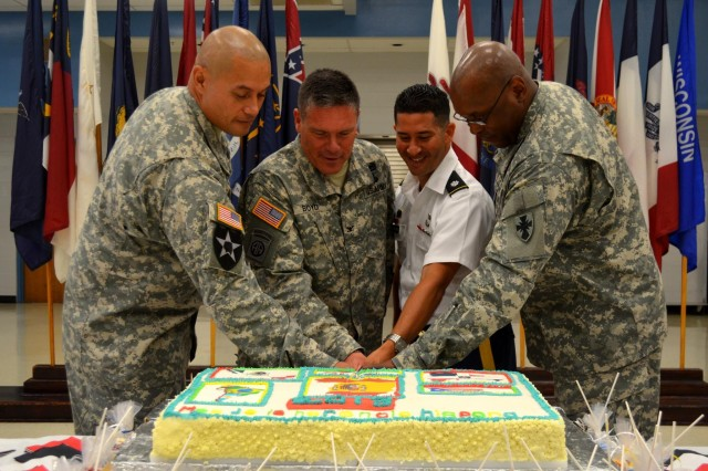 Lt. Col. Alberto Rodriguez, chief of future operations for the 8th Theater Sustainment Command, cuts into the cake with Col. Gregory Boyd and Command Sgt. Maj. Toese Tia, command team for the 45th Sustainment Brigade, during the Hispanic Heritage celebration Oct. 2 at the Fort Shafter Flats. (U.S. Army photo by Spc. Erin Sherwood, 45th Sustainment Brigade Public Affairs)