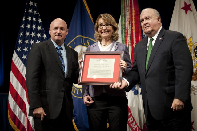 """Under Secretary of the Army Joseph W. Westphal (far right) presents the Army Decoration for Distinguished Civilian Service to former Rep. Gabrielle """"Gabby"""" Giffords (Ariz.) for """"outstanding public service and support of the Army's missions,"""" Oct. 10, 2013, at the Pentagon. She is joined by her husband retired Navy Capt. Mark Kelly."""