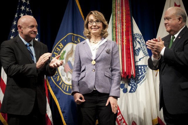 "Former Rep. Gabrielle ""Gabby"" Giffords (Ariz.) being applauded by Under Secretary of the Army Joseph W. Westphal (far right) and her husband retired Navy Capt. Mark Kelly (far left), just after she was presented with the Army Decoration for Distinguished Civilian Service for ""outstanding public service and support of the Army's missions,"" Oct. 10, 2013, at the Pentagon."