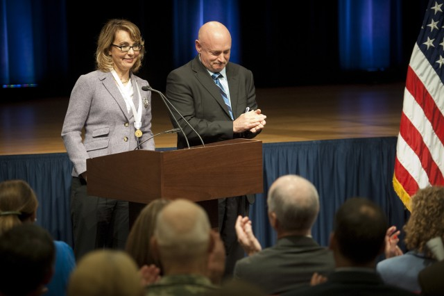 """Former Rep. Gabrielle """"Gabby"""" Giffords (Ariz.) being applauded by her husband retired Navy Capt. Mark Kelly as well as the rest of the audience, during her remarks just after she was presented with the Army Decoration for Distinguished Civilian Service for """"outstanding public service and support of the Army's missions,"""" Oct. 10, 2013, at the Pentagon."""