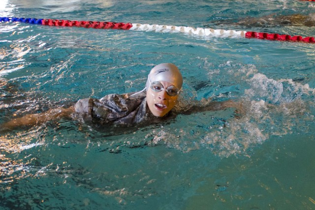 While wearing her full ACUs, Capt. Erika Huerta, aide de camp to the USAPHC commanding general, swims 100 meters during the German Armed Forces Proficiency Badge competition.