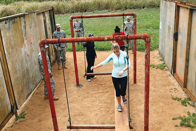 Military spouses tackle a leadership reaction obstacle course, with supervision from Soldiers, during the Joint Spouses' Conference, Oct. 5.