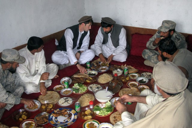 Dressed in traditional Afghan clothing, Capt. William D. Swenson (left center) joins village elders for a meal to discuss what the coalition can do to help the local community. In support of the 10th Mountain Division (Light Infantry), Swenson served as an embedded trainer and mentor for the Afghan Border Police. He is slated to receive the Medal of Honor, Oct. 15, 2013, for his actions Sept. 8, 2009, in the Battle of Ganjgal, Afghanistan.