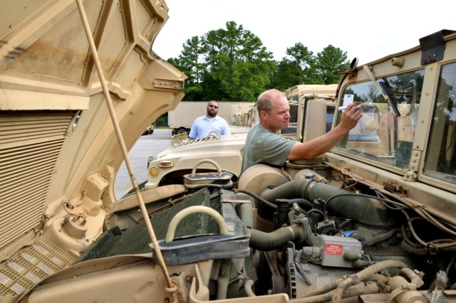Kevin Koch, background, and Tom Lundman, both from the TACOM Security Assistance Management Directorate, inspect Humvees, or High-Mobility Multipurpose Wheeled Vehicles, during a Joint Vehicle Inspection for the government of Thailand at Redstone Arsenal's Defense Logistics Agency Disposition Services. The inspection is part of the Army's Foreign Military Sales process.