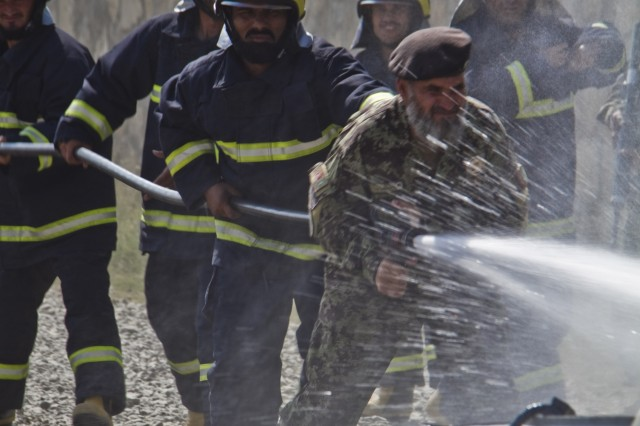 """KHOWST PROVINCE, Afghanistan """" Led by their commander, Afghan National Army firemen utilize a fire-hose to put out a simulated fire during a mass-casualty exercise on Camp Parsa, Afghanistan, Oct. 12, 2013. (U.S. Army photo by Sgt. Justin A. Moeller, 4th Brigade Combat Team Public Affairs)"""