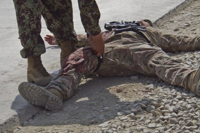 """KHOWST PROVINCE, Afghanistan """" A medic with the Afghan National Army applies a tourniquet to a simulated casualty during a mass-casualty exercise on Camp Parsa, Afghanistan, Oct. 12, 2013. (U.S. Army photo by Sgt. Justin A. Moeller, 4th Brigade Combat Team Public Affairs)"""