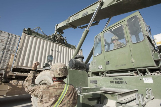 South Dakota Army National Guard Staff Sgt. Adam Holen, 152nd Combat Sustainment Support Battalion, of Volga, S.D., operates a rough terrain container handler to place a container onto the back of a palletized load system, with the guidance from Maryland Army National Guard Staff Sgt. Jim Blakeley, 1129th Transportation Company, at Kandahar Airfield, Afghanistan, Oct. 8, 2013. The 152nd CSSB is working to not only sustain the four transportation units and the ordnance company they manage at Kandahar Airfield, they are also helping units in Regional Command-South drawdown equipment.