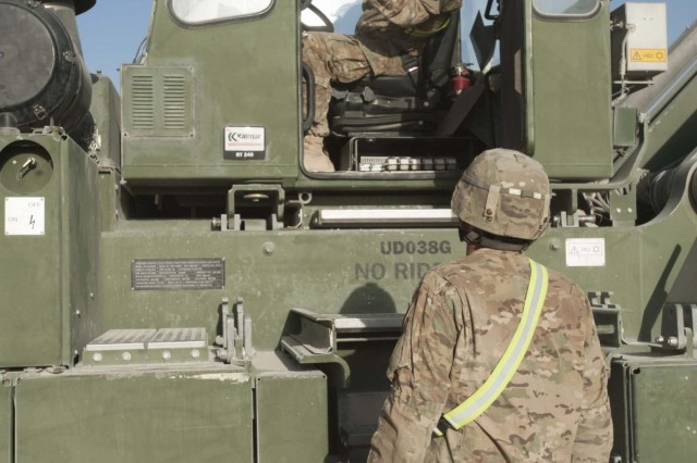 South Dakota Army National Guard Staff Sgt. Adam Holen, 152nd Combat Sustainment Support Battalion, of Volga, S.D., operates a rough terrain container handler to move containers with the guidance of Maryland Army National Guard Staff Sgt. Jim Blakeley, 1129th Transportation Company, at Kandahar Airfield, Afghanistan, Oct. 8, 2013. The 152nd CSSB is working to not only sustain the four transportation units and the ordnance company they manage at Kandahar Airfield, they are also helping units in Regional Command-South drawdown equipment.