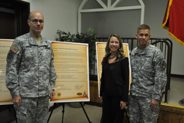 Brig. Gen. Chris. R. Gentry, deputy commander of Eighth Army, Barbara Barnett, a victim advocate at Army Community Services, and Col. Michael. E. Masley, commander of U.S. Army Garrison Yongsan pose in front of the domestic violence awareness proclamations that they have signed, Oct. 1. (U.S. Army photo by Cpl. Jung Jihoon)