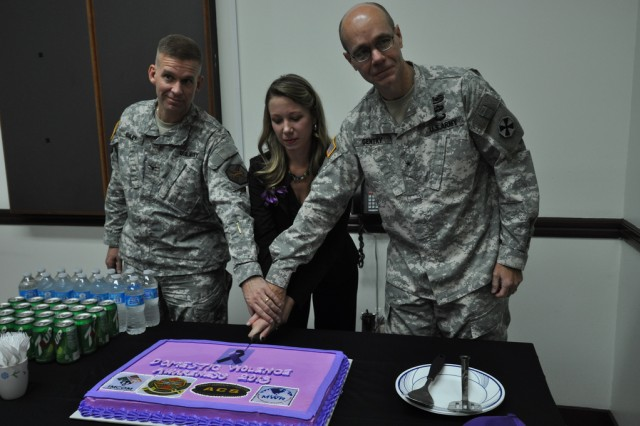 Col. Michael. E. Masley, commander of U.S. Army Garrison Yongsan, Barbara Barnett, a victim advocate at Army Community Services, and Brig. Gen. Chris. R. Gentry, deputy commander of Eighth Army, cut a purple cake after the Domestic Violence Awareness Ceremony, Oct. 1. Purple is the color of domestic violence awareness. (U.S. Army photo by Cpl. Jung Jihoon)