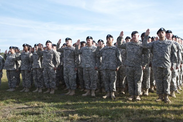 """Eighty-four """"Spartan"""" Soldiers of the 2nd Armored Brigade Combat Team, 3rd Infantry Division, raise their right hand as they recite the Oath of Re-enlistment in a ceremony at Cottrell Field, Fort Stewart, Ga., Oct. 3, 2013. Hundreds of family, friends and fellow Soldiers came out to watch and support the Soldiers as they re-enlisted."""