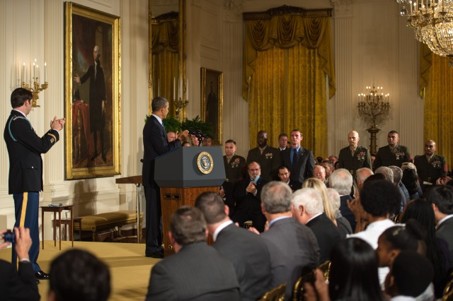 Former Army Capt. William D. Swenson, President Barack Obama and those in attendance applaud fellow service members at the East Room of the White House in Washington, D.C., on October 15, 2013. Swenson is being awarded the Medal of Honor for his actions in a lengthy battle against the Taliban insurgents in the Ganjgal Valley on September 8, 2009. (U.S. Army Photo by Sgt. Mikki L. Sprenkle/Released)
