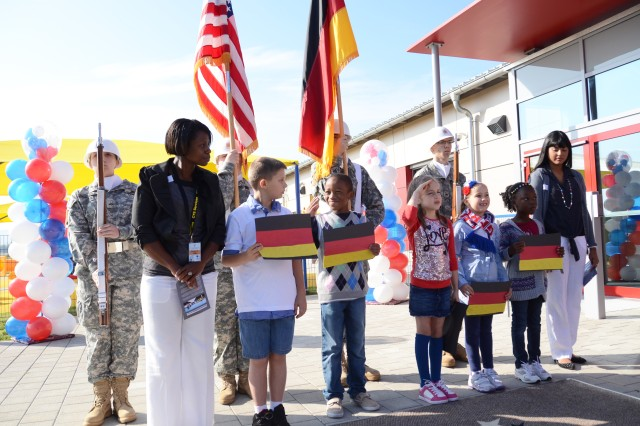 "Children from the Storck Child Development and School Age Center, joined by members of the U.S. Army Garrison Ansbach Junior ROTC and of USAG Ansbach's Child, Youth and School Services team, prepare to render honors at the start of the singing of the German national anthem, ""Das Lied der Deutschen,"" during the grand opening of the new Storck Barracks CYS Services Complex."