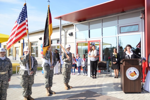 Trude Moellmann, right, director of Parent and Outreach Services for U.S. Army Garrison Ansbach Child, Youth and School Services, welcomes attendees to the Storck Barracks Child, Youth and School Services Complex grand opening and ribbon-cutting ceremony Sept. 28.