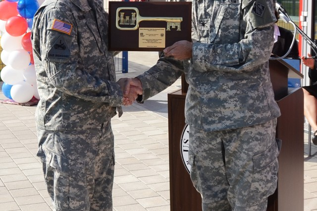 Col. D. Peter Helmlinger, commander of U.S. Army Corps of Engineers, Europe District, right, presents a plaque on behalf of USACE during the Storck Barracks Child, Youth and School Services Complex grand-opening ceremony Sept. 28.
