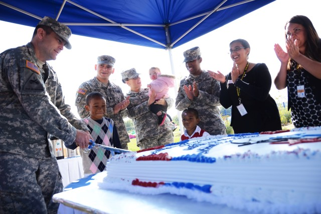Col. Christopher M. Benson, U.S. Army Garrison Ansbach commander, helps a young member of the Storck Child Development and School Age Center cut the cake Sept. 28 during the Storck Barracks Child, Youth and School Services Complex grand opening.