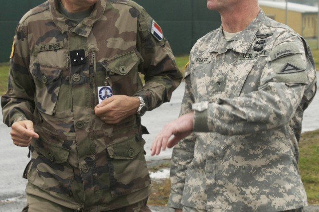 French Maj. Gen. Jean Fred Berger, commander of the Joint Warfare Centre in Stavenger, Norway, in discussion with Brig. Gen. Walter E. Piatt, commander of the 7th Army Joint Multinational Training Command, during exercise Unified Endeavor, at Camp Aachen in the Grafenwoehr Training Area, Germany, Oct 15, 2013. Unified Endeavor is a multi-tiered command post mission rehearsal exercise, primarily hosted by U.S. Army Europe's Joint Multinational Training Command, to train the next headquarters for the International Security Assistance Force mission in Afghanistan.