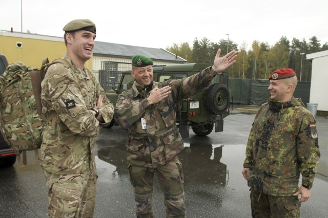 U.K. Maj. Richard Dobson (left), French Maj. Phillippe Baillot (center) and German Maj. Peter Leffler share a light-hearted moment during a break in meetings, during exercise Unified Endeavor at JMTCs Camp Aachen in the Grafenwoehr Training Area, Germany, Oct 15, 2013. The three majors represent only three of the 24 nation participants attending the exercise. Unified Endeavor is a multi-tiered command post mission rehearsal exercise, primarily hosted by U.S. Army Europe's Joint Multinational Training Command to train the next headquarters for the International Security Assistance Force mission in Afghanistan.