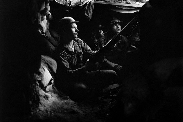 Infantrymen of the 27th Infantry Regiment, near Heartbreak Ridge, take advantage of cover and concealment in tunnel positions, 40 yards from the Communists. August 10, 1952.