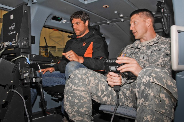 Chief Warrant Officer 3 Scott Sauer (right) explains the controls of a LUH-72 Lakota to Walt Rada at Aberdeen Proving Ground, Md., Sept. 25.