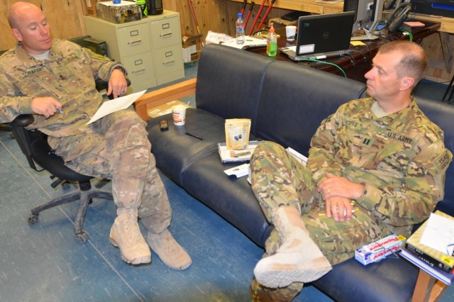 First Sgt. Jeffrey Schafer, left, and Chaplain (Capt.) Kevin Trimble, right, discusses upcoming events and issues ranging from classes for financial security to soldiers needing assistance for Headquarters and Headquarters Company, Task Force Gunfighters, 1st Combat Aviation Brigade, 1st Infantry Division at Multinational Base Tarin Kot, Afghanistan, Sept. 18, 2013. (U.S. Army photo by Capt. Andrew Cochran/released)