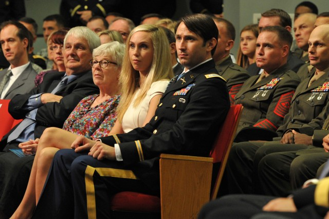 Former Army Capt. William D. Swenson (center) sits with his significant other Kelsey Long, and his parents Julia Buchholz and Carl Swenson, at his induction ceremony into the Pentagon Hall of Heroes, Oct. 16, 2013. Behind Swenson are several of the Marines who served with him at the Battle of Ganjgal, Afghanistan, Sept. 8, 2009.